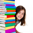 Student sitting behind pile of books on white - Stock Photo