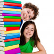Photo: Students sitting behind pile of books on white