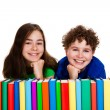 Stock Photo: Students sitting behind pile of books on white