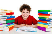 Boy behind pile of books isolated on white background — Stock Photo