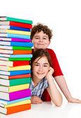Studenci siedząc za stos książek na biały — Zdjęcie stockowe