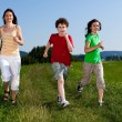 Active family - mother and kids running, jumping outdoor — Stock Photo #8595097