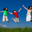 Active family - mother and kids jumping outdoor — Stock Photo #8595113