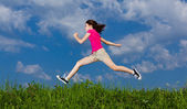 Girl jumping, running against blue sky — Stockfoto