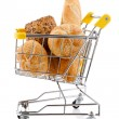 Shopping trolley full of bread and rolls on white background — Stock Photo