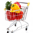 Shopping trolley full of pepper on white background — Stock Photo