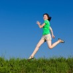 Girl jumping, running against blue sky — Stock Photo