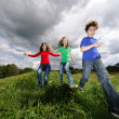 Active family - mother and kids running, jumping outdoor — Stockfoto