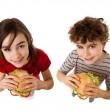Kids eating big sandwich isolated on white background — Stock Photo