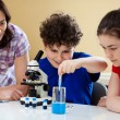 Kids examining preparation under the microscope — Stock Photo #8764791