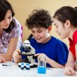 Kids examining preparation under the microscope — Stock Photo