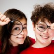 Girl and boy holding magnifying glass - Stok fotoğraf