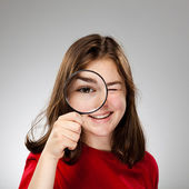 Girl holding magnifying glass — Stok fotoğraf