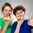 Kids eating cake with cream and fruits — Stock Photo #9534435