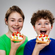 Kids eating cake with cream and fruits — Stock Photo #9534491
