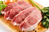 Cerdo cruda en la tabla de cortar y verduras — Foto de Stock