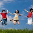 Active family - mother and kids jumping outdoor — Stockfoto #9657325