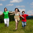 Stock Photo: Active family - mother and kids running, jumping outdoor