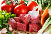 Raw beef on cutting board and vegetables — Stock Photo