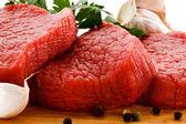 Rohe rindfleisch auf schneidebrett und gemüse — Stockfoto