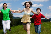 Active family - mother and kids running, jumping outdoor — Foto de Stock