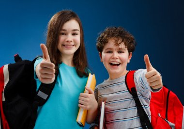 Students showing OK sign on blue background