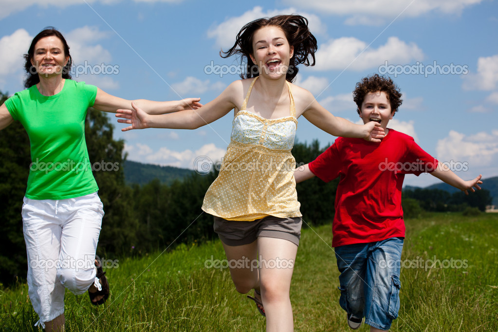 Active family - mother and kids running, jumping outdoor against blue sky  — Stok fotoğraf #9657343