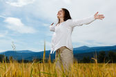 Girl holding arms up against blue sky — Stock Photo