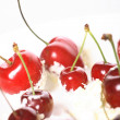 Cream, cherries on a white background — Stock Photo