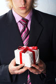 Man holiday and offering a gift on his hand — Stock Photo