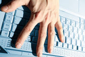 Close-up of hand touching computer keys during work — Stock Photo