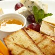 Cheese plate with grapes and honey - Foto Stock