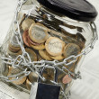 Coins in money jar - Foto Stock