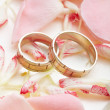 Golden rings and rose petals - Stockfoto