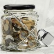 Coins in money jar - Stock Photo