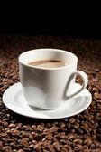 Cup with coffee, costing on coffee grain — Stockfoto