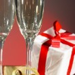 Glasses of champagne, gifts with red tapes and bows — Stock Photo #9843675
