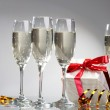 Glasses of champagne, gifts with red tapes and bows — Stock Photo #9866150