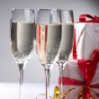Glasses of champagne, gifts with red tapes and bows — Stock Photo