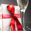 Glasses of champagne, gifts with red tapes and bows -  