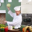 Young chef preparing lunch in kitchen — Stock Photo
