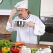 Stock Photo: Young Chef tasting food with tablespoon