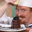 Funny young chef added chocolate sauce at piece of cake — Stock Photo #9060048