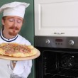 Young chef smelling italian pizza in kitchen — Stock Photo
