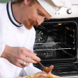 Young chef prepared italian pizza in kitchen — Stock Photo #9060109