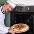 Young chef with italian pizza in kitchen — Stock Photo