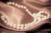 Pearls on the satin — Stock Photo