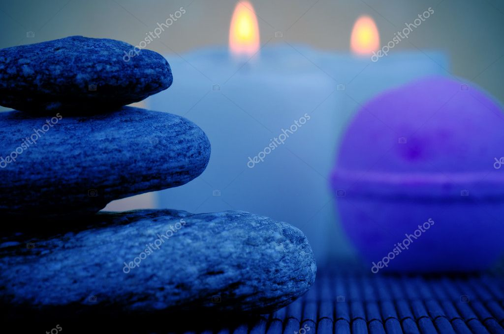 Pile of stones, soap and burning candles in the background — Stock Photo #9688345