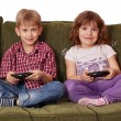 Stock Photo: Boy and little girl play video game