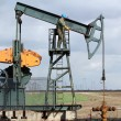 Photo: Oil and fuel industry oil worker standing on pump jack